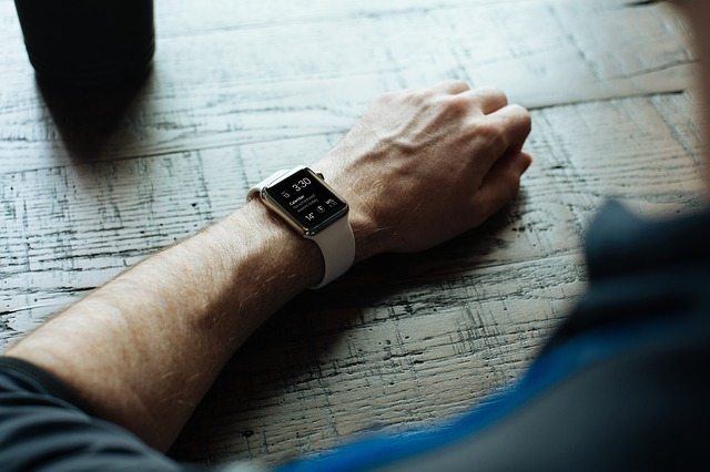 An Apple watch on the wrist of a man looking at antique watches-Pieces of Time