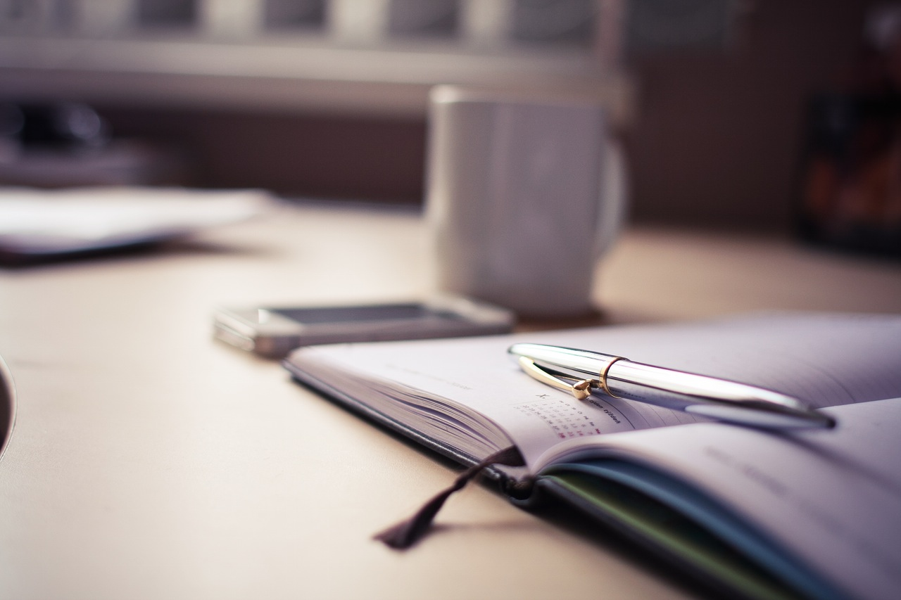 Desk planner on office desk allows for time to be planned.